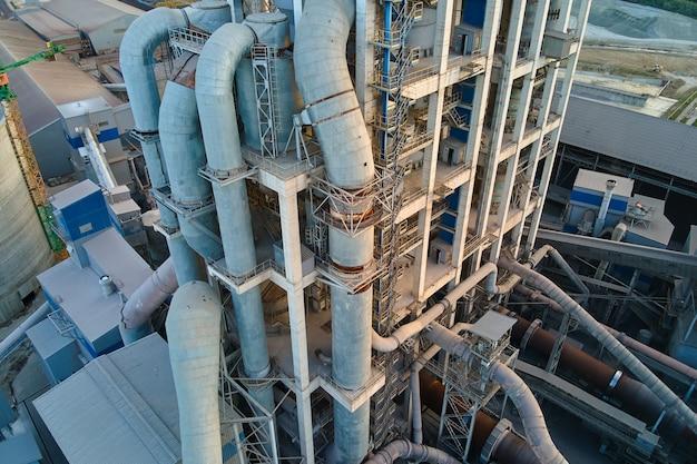 Luftaufnahme der zementfabrik mit hoher betonwerksstruktur und turmdrehkran am industriellen produktionsstandort. herstellung und globales industriekonzept.