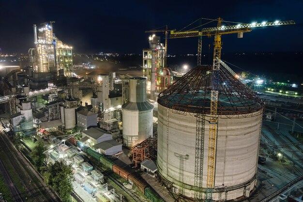 Luftaufnahme der zementfabrik mit hoher betonwerksstruktur und turmdrehkranen im industriellen produktionsbereich nachts. herstellung und globales industriekonzept.