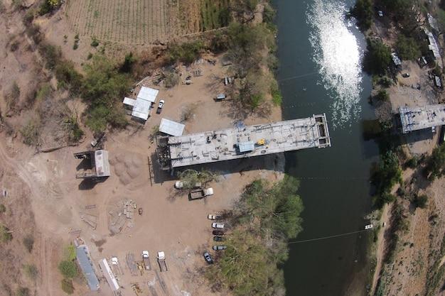 Luftaufnahme des bauprozesses einer brücke über einen fluss