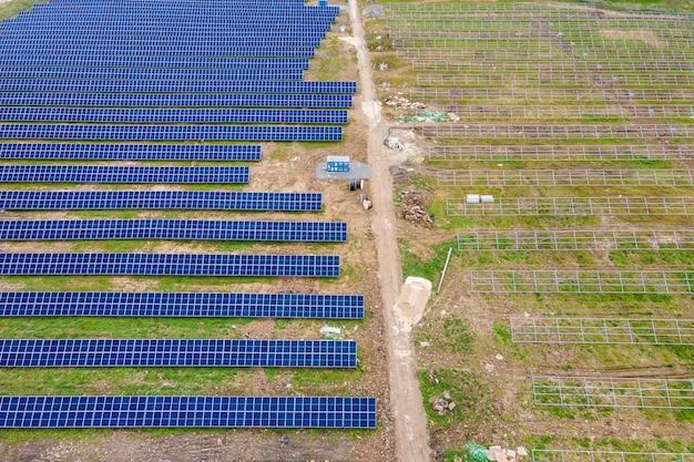 Luftaufnahme des baus großer kraftwerke mit vielen reihen von sonnenkollektoren auf metallrahmen zur erzeugung sauberer ökologischer elektrischer energie. entwicklung erneuerbarer stromquellen.