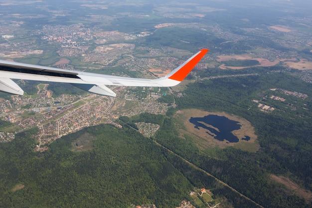 Luftaufnahme des blauen himmels der wolke und der flachen flügelansicht durch das flugzeugfenster,