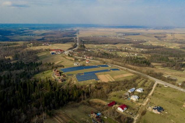 Luftaufnahme des blauen solar-photovoltaik-paneelsystems, das erneuerbare saubere energie auf ländlicher landschaft erzeugt