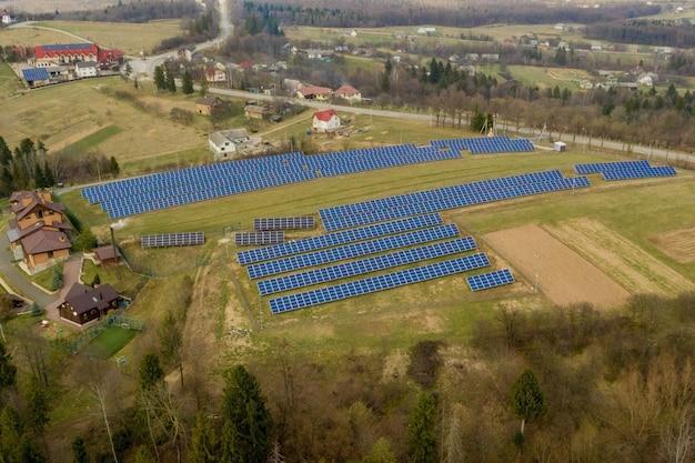 Luftaufnahme des blauen solar-photovoltaikmodulsystems, das erneuerbare saubere energie auf ländlicher landschaft erzeugt