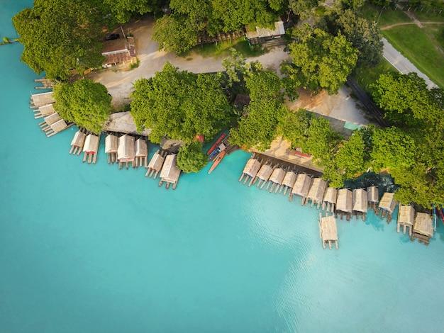 Luftaufnahme des blauen wasserflusses, draufsicht des blauen lagunen-teichwassers von oben, vogelperspektive grüner baum und bambusfloßhaus und holzboot auf der wasseroberfläche schöne frische umgebung landschaftssee