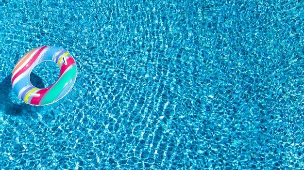 Luftaufnahme des bunten aufblasbaren ringkrapfenspielzeugs im schwimmbadwasser von oben