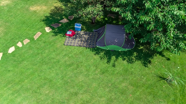 Luftaufnahme des campingplatzes von oben, zelt und campingausrüstung unter baum