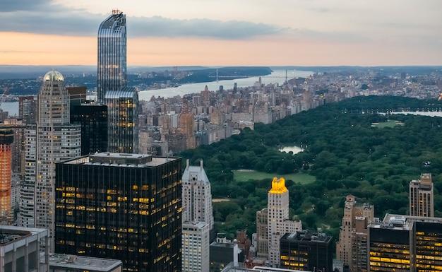Luftaufnahme des central park in der abenddämmerung in manhattan, new york city, mit wolkenkratzern im vordergrund