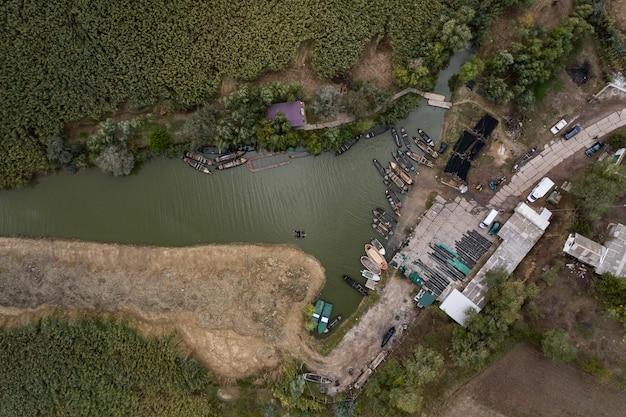 Luftaufnahme des fischerpierdocks mit vielen fischerbooten, die in einem hafen geparkt werden. vogelperspektive von oben des kleinen fischereihafens.