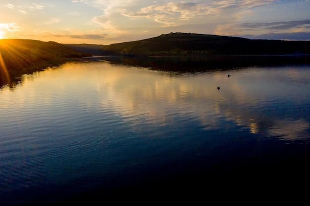 Luftaufnahme des fischers am boot auf goldenem sonnenuntergangsfluss. silhouette der fischer mit seinem boot, fischer lebensstil.