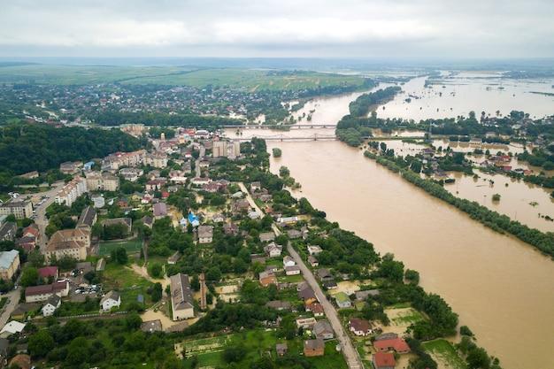 Luftaufnahme des flusses dnister mit schmutzigem wasser und überfluteten häusern in der stadt halych, westukraine.