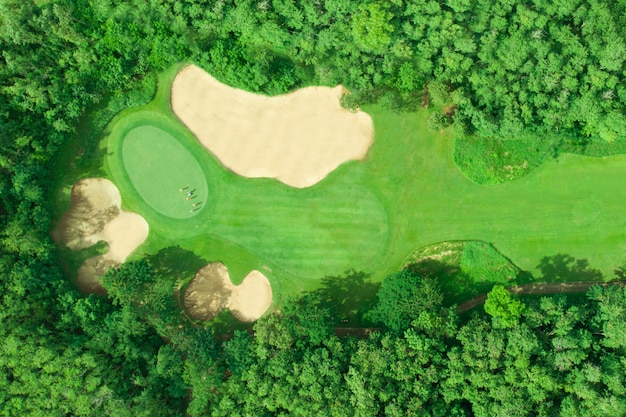 Luftaufnahme des golfplatzes mit den golfspielern, die den golfball auf ein grün setzen
