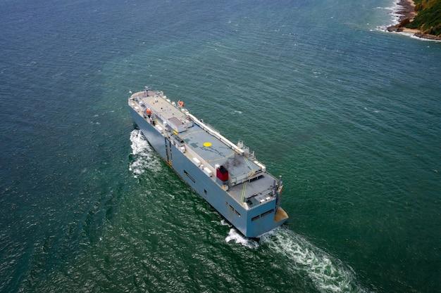 Luftaufnahme des großen roro-fahrzeugträgerschiffs, das auf dem grünen meer segelt