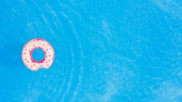 Luftaufnahme des großen rosa donuts im schwimmbadhintergrund