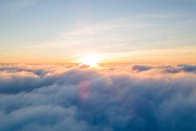 Luftaufnahme des hellen gelben sonnenuntergangs über weißen dichten wolken mit blauem himmel über ihnen.