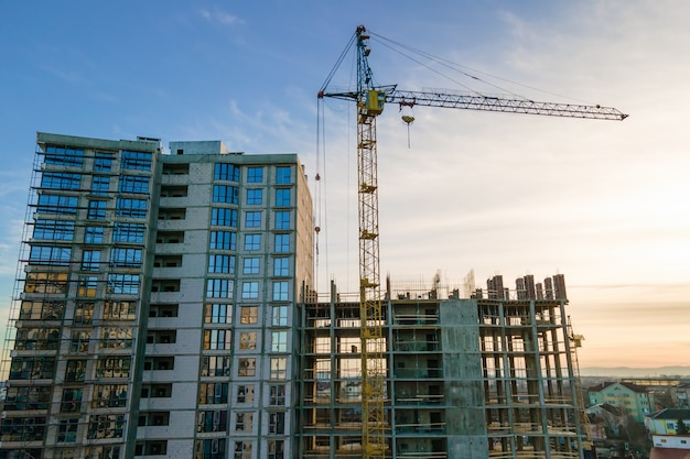 Luftaufnahme des hohen turmdrehkrans und des im bau befindlichen wohnhauses bei sonnenuntergang. immobilien-entwicklung.