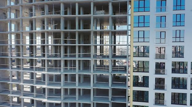Luftaufnahme des hohen wohngebäudes im bau. viele fenster an der fassade des neuen apartmentgebäudes im bau. immobilien-entwicklung.