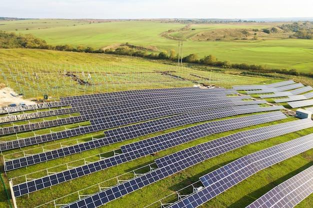 Luftaufnahme des im bau befindlichen solarkraftwerks auf der grünen wiese. montage von schalttafeln zur erzeugung sauberer ökologischer energie.