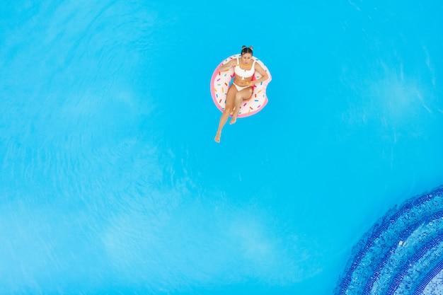 Luftaufnahme des jungen schönen mädchens in einem weißen bikini, der auf aufblasbarem donut im pool entspannt. sommerferienhintergrund