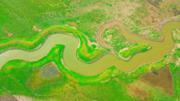 Luftaufnahme des kanals unter den wiesen in der sonnenuntergangzeit