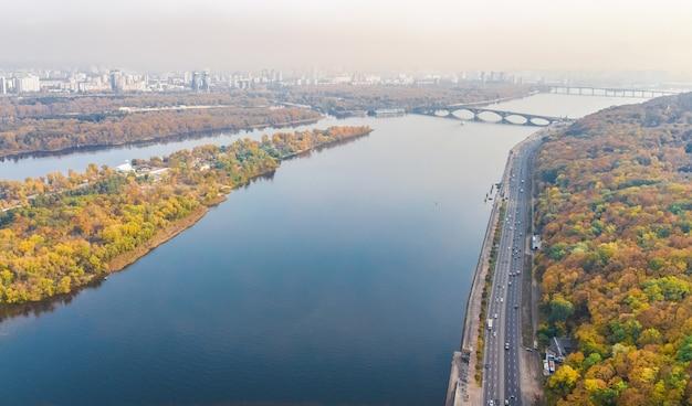 Luftaufnahme des kiewer herbststadtbildes und -parks, fluss dnjepr, insel truchaniv und brücken von oben, skyline der stadt kiew, ukraine