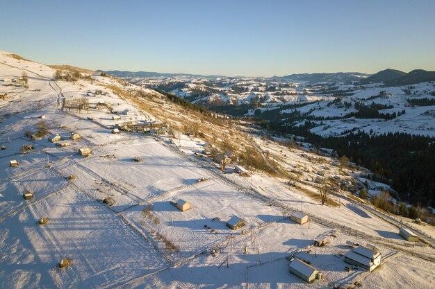 Luftaufnahme des kleinen dorfes mit verstreuten häusern auf schneebedeckten hügeln im winter