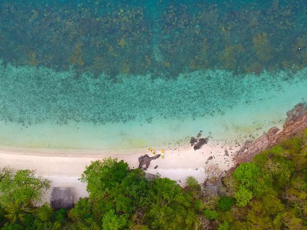 Luftaufnahme des korallenriffs und des küstenhauses mit kajakanker nahe einem riff