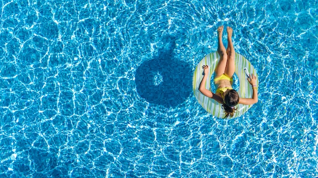 Luftaufnahme des mädchens im schwimmbad von oben, kind schwimmen auf aufblasbarem ringkrapfen und hat spaß im wasser im familienurlaub