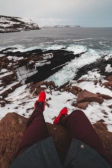 Luftaufnahme des mannes, der auf einer bergklippe sitzt, die das meer übersieht