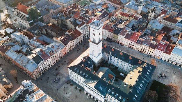 Luftaufnahme des marktplatzes in der altstadt von lemberg, ukraine. rathaus mit ukrainischer nationalflagge und marktplatz