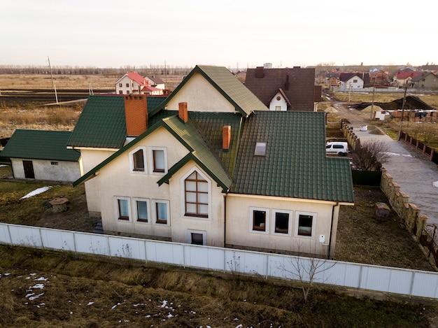 Luftaufnahme des neuen wohnhaushauses und der garage oder scheune mit schindeldach auf eingezäuntem hof am sonnigen tag.