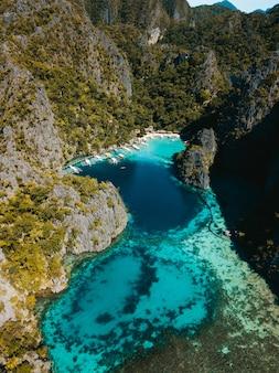 Luftaufnahme des ozeans, umgeben von schönen bergen, die mit grüns bedeckt sind