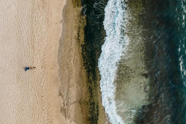 Luftaufnahme des sandes, der das meerwasser und die wellen trifft