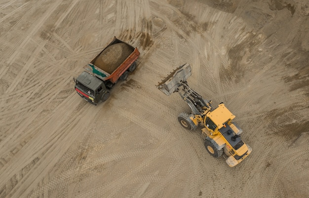 Luftaufnahme des sandsteinbruchs. bulldozer gießt sand in lkw