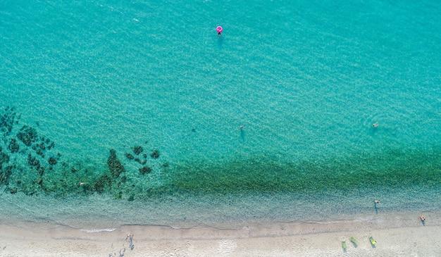 Luftaufnahme des sandstrandes mit schwimmenden touristen.