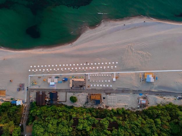 Luftaufnahme des sandstrandes mit sonnenschirmen, meer und wald an der ostsee in yantarny bei sonnenuntergang