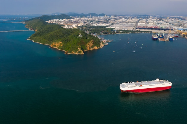 Luftaufnahme des schiffes, das neue autos lädt. kfz-containerträger übersee-dienste. transportgeschäft für fertighäuser per seefracht.