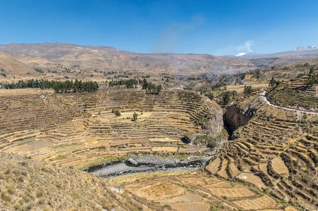 Luftaufnahme des schönen colca canyon unter dem blauen himmel, der in peru gefangen genommen wird