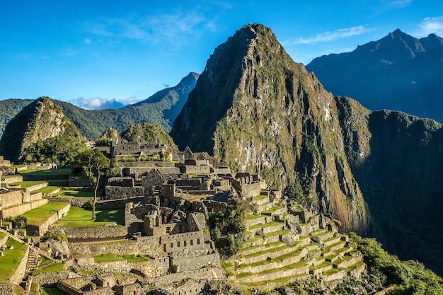 Luftaufnahme des schönen dorfes durch den berg, der in machu picchu, peru gefangen genommen wird