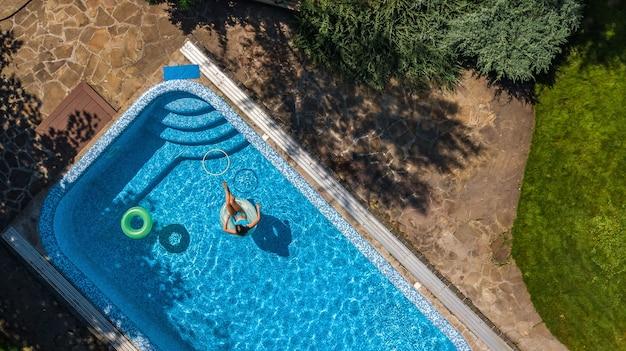 Luftaufnahme des schönen mädchens im schwimmbad von oben, schwimmen auf aufblasbarem ringkrapfen und hat spaß im wasser auf tropischem ferienort