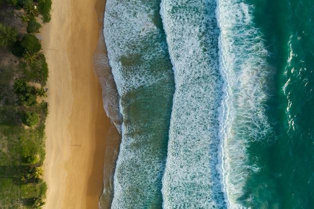 Luftaufnahme des schönen wellenmeers weißer meeresschaum am tropischen strand meereswelle, die auf sandigen ufern abstürzt, leerer und sauberer strand bei sonnenuntergang oder sonnenaufgang schöner strand von phuket thailand.
