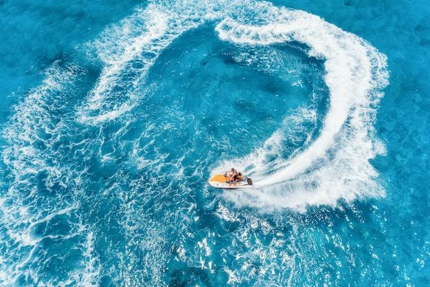 Luftaufnahme des schwimmenden wasserscooters im blauen wasser am sonnigen tag im sommer