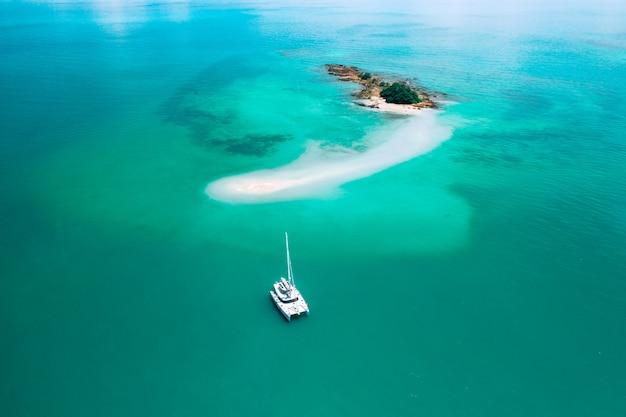 Luftaufnahme des segelboots verankernd auf korallenriff. vogelperspektive, wassersportthema.