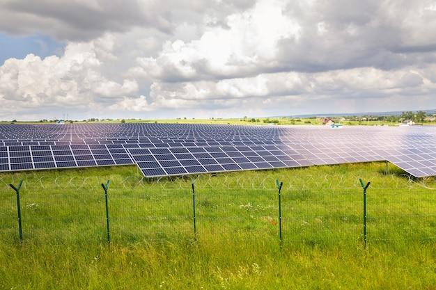 Luftaufnahme des solarkraftwerks auf der grünen wiese mit schutzdrahtzaun um ihn herum. schalttafeln zur erzeugung sauberer ökologischer energie.