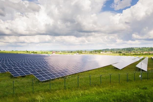 Luftaufnahme des solarkraftwerks auf der grünen wiese mit schutzdrahtzaun um sie herum. schalttafeln zur erzeugung sauberer ökologischer energie.