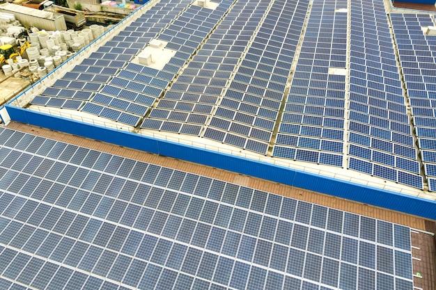 Luftaufnahme des solarkraftwerks mit blauen photovoltaikpaneelen, die auf dem dach des industriegebäudes montiert sind.