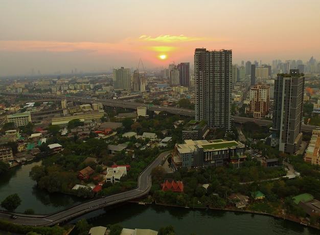Luftaufnahme des sonnenuntergangs über wohnviertel von bangkok urban, thailand von drone