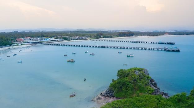 Luftaufnahme des strandes mit anlegestelle und vielen fischerboot im meer nahe der felseninsel.