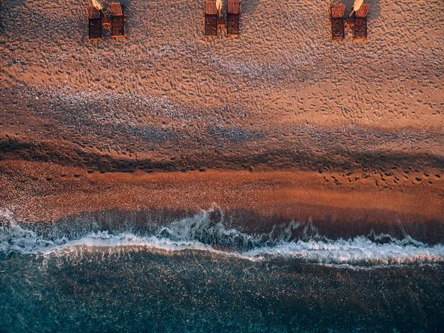 Luftaufnahme des strandes mit liegestühlen nahe der insel sveti stefan in montenegro