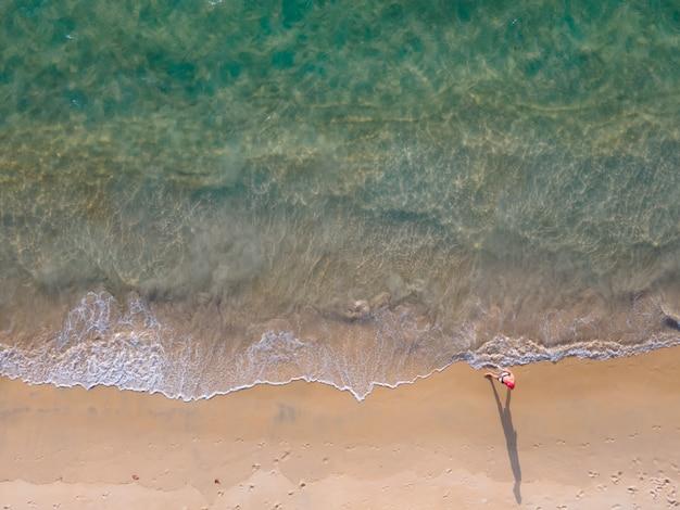 Luftaufnahme des strandes und einer person, die am großen ufer entlang geht