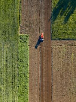 Luftaufnahme des traktors auf der landwirtschaftlichen feldsaat. traktoren, die im frühjahr auf dem landwirtschaftlichen feld arbeiten. foto von drohne
